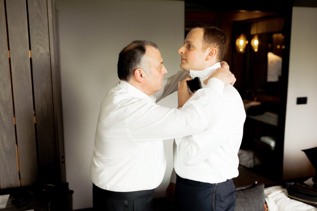 Groom's father tying a groom's bowtie around his neck at Liberty Warehouse in Brooklyn, New York.