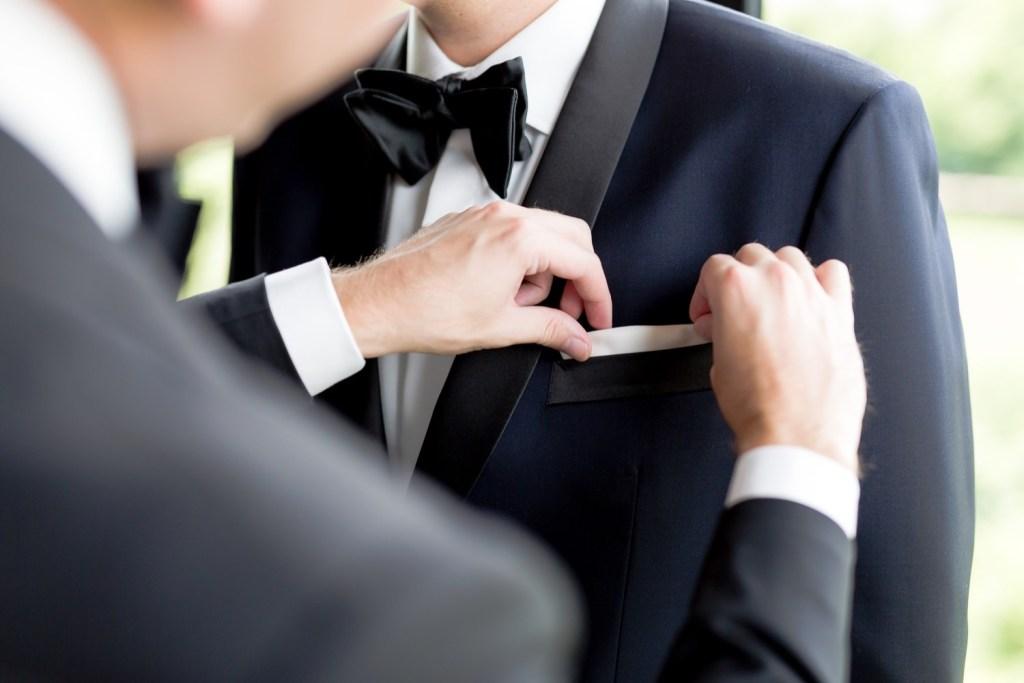 A groomsman putting a handkerchief inside a pocket handkerchief at Liberty Warehouse in Brooklyn, New York.