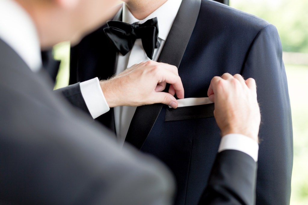 A groomsman putting a handkerchief inside a pocket handkerchief at Liberty Warehouse in Brooklyn, New York.