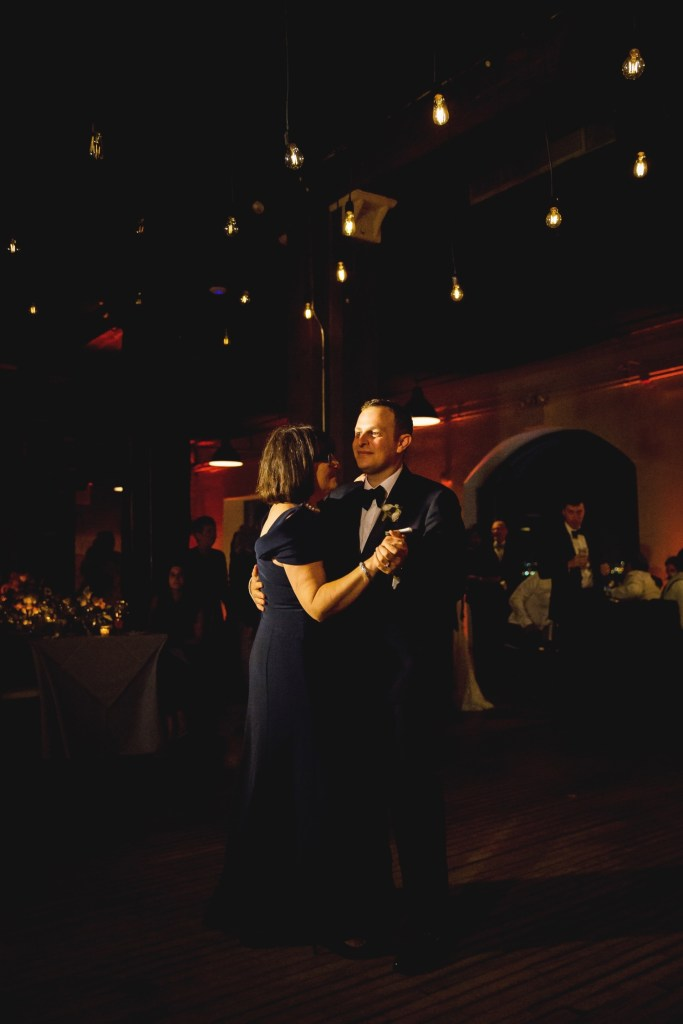 A groom dancing with her mother during a wedding reception at Liberty Warehouse, Brooklyn New York.