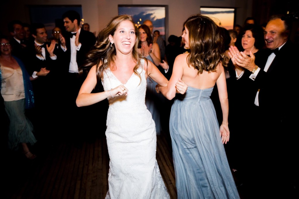 A bride dancing with her wedding guests during her wedding reception at Liberty Warehouse, Brooklyn New York.