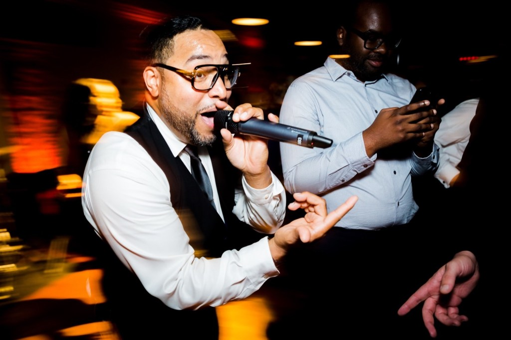 A singing singer during a wedding reception at Liberty Warehouse, Brooklyn New York.