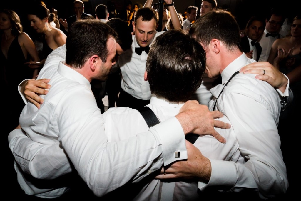 A groom and groomsmen huddling during their wedding reception at Liberty Warehouse, Brooklyn New York.