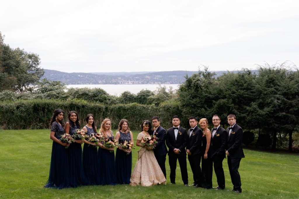 A wedding couple and their wedding party posing for a picture at the Tappan Hill Mansion.