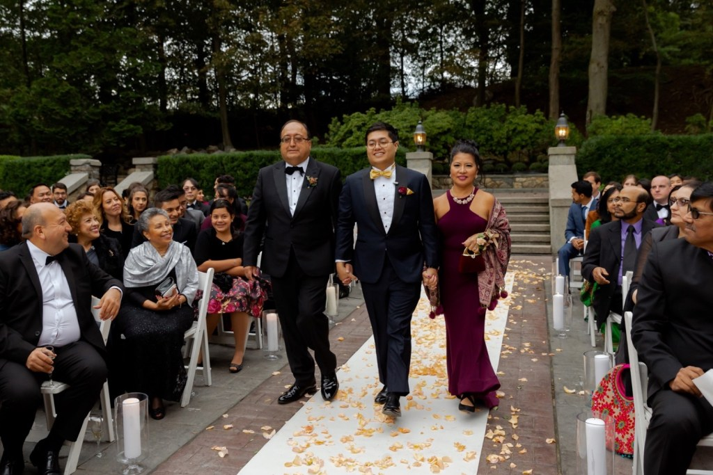 A groom and his parent walking towards the ceremony at the Tappan Hill Mansion.