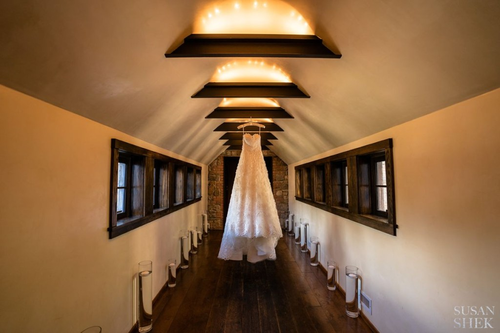 wedding dress hanging in the hallway of the haybarn of blue hill stone barns
