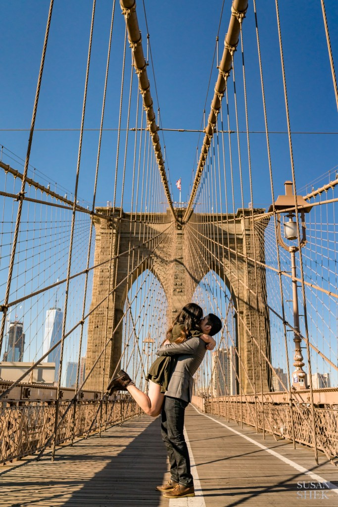 couple being photographed on brooklyn bridge facing manhattan skyline