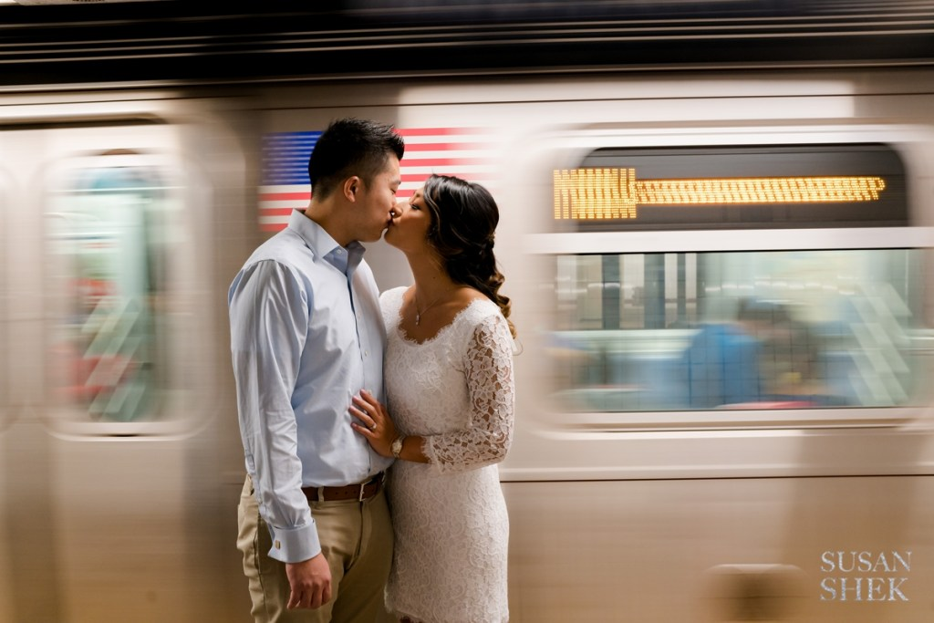 A photo of a couple standing near a subway passing by.