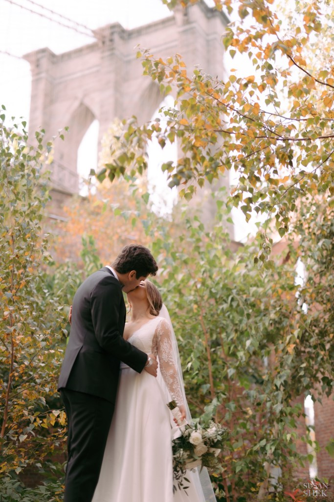 couple kissing by brooklyn bridge