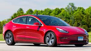 red Tesla car on roadway