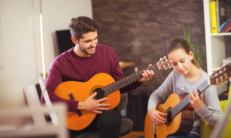 Guitar teacher teaching the little girl