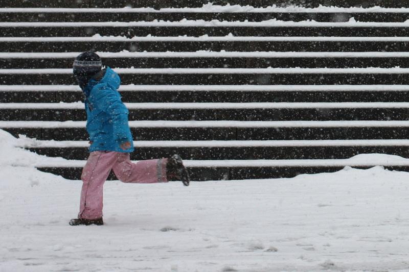 Tübingen, Kind schlittert auf Schnee vor der Stiftskirchentreppe