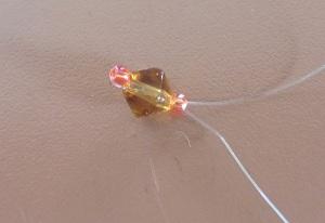 Armband met kralensluiting beide draden door de derde kraal