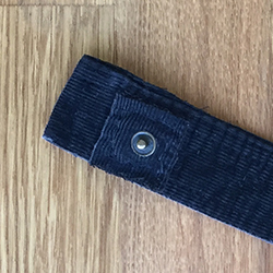 Closeup view of the snap post sewn on the wrong side of the snap head strip for a bicycle pant leg keeper