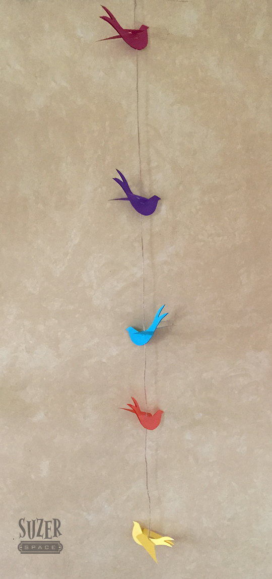 A string of paper swallows made from a patten found at the krokotak website
