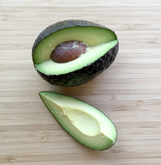 Cutting an avocado into quarters is a safer way to remove the pit
