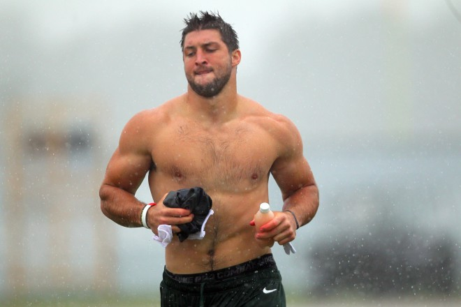 Tim Tebow runs off the field shirtless during a New York Jets field practice at training camp, in the rain.