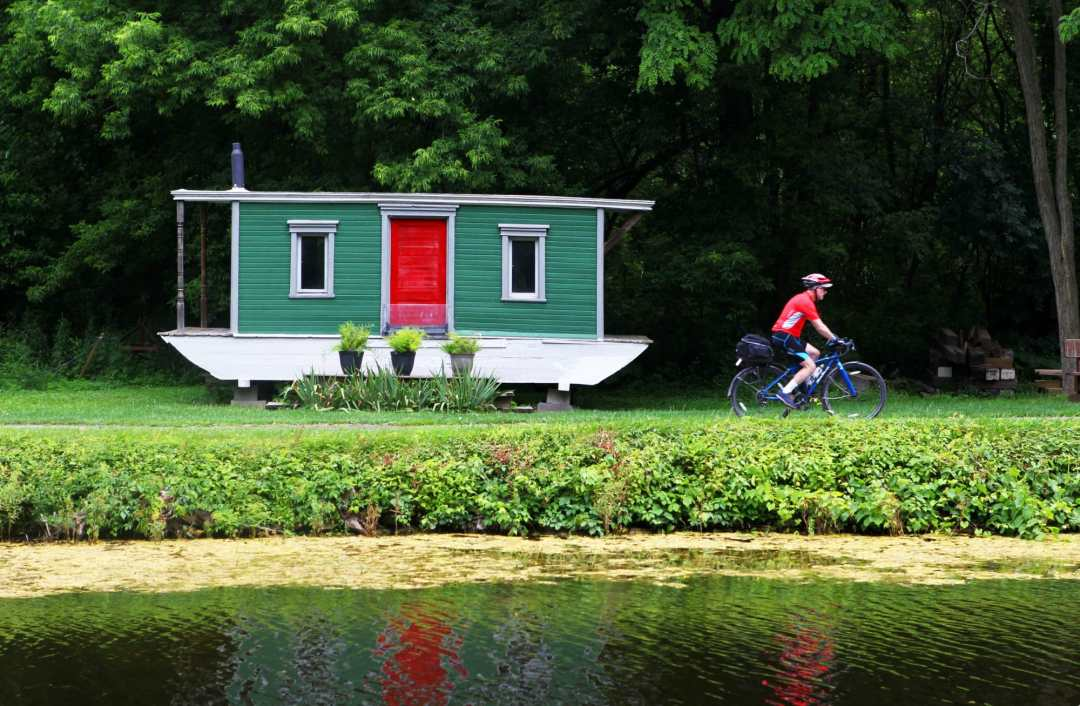 A cyclist rides past a red door of a houseboat, used as a home, in summer, along the Erie Canalway Trail, part of the longer Empire State Trail in New York State.