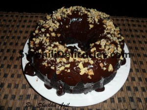 Chocolate cake with chocolate ganache and chopped walnuts.