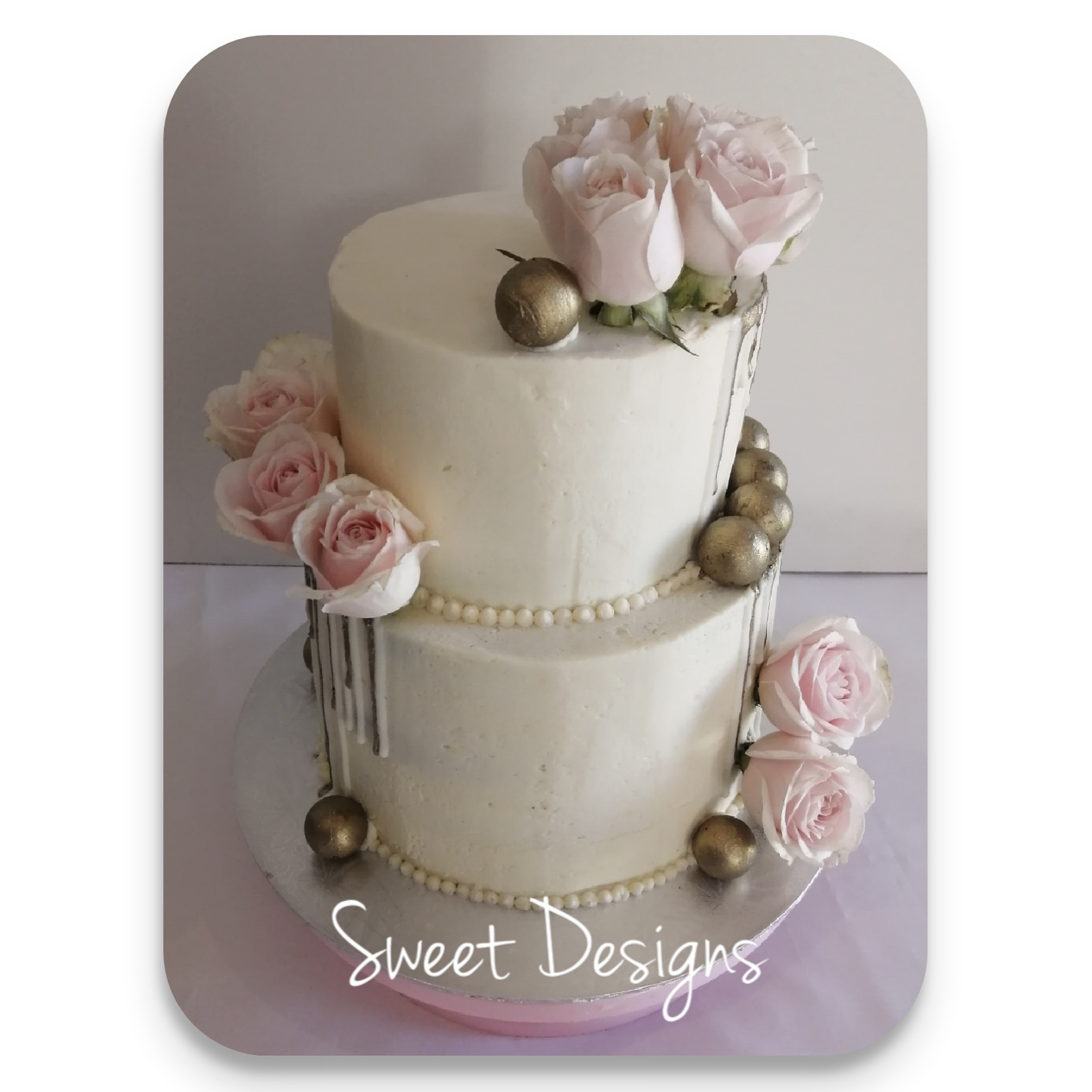 Buttercream Cake with fresh flowers and golden chocolate balls