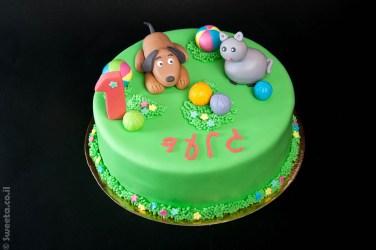 עוגה מעוצבת ליום הולדת של גיל שנה עם כלב חתול והרבה כדורים מבצק סוכר