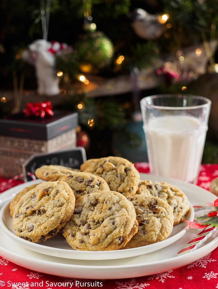Chewy Chocolate Chip Cookies on white dish with glass of milk.