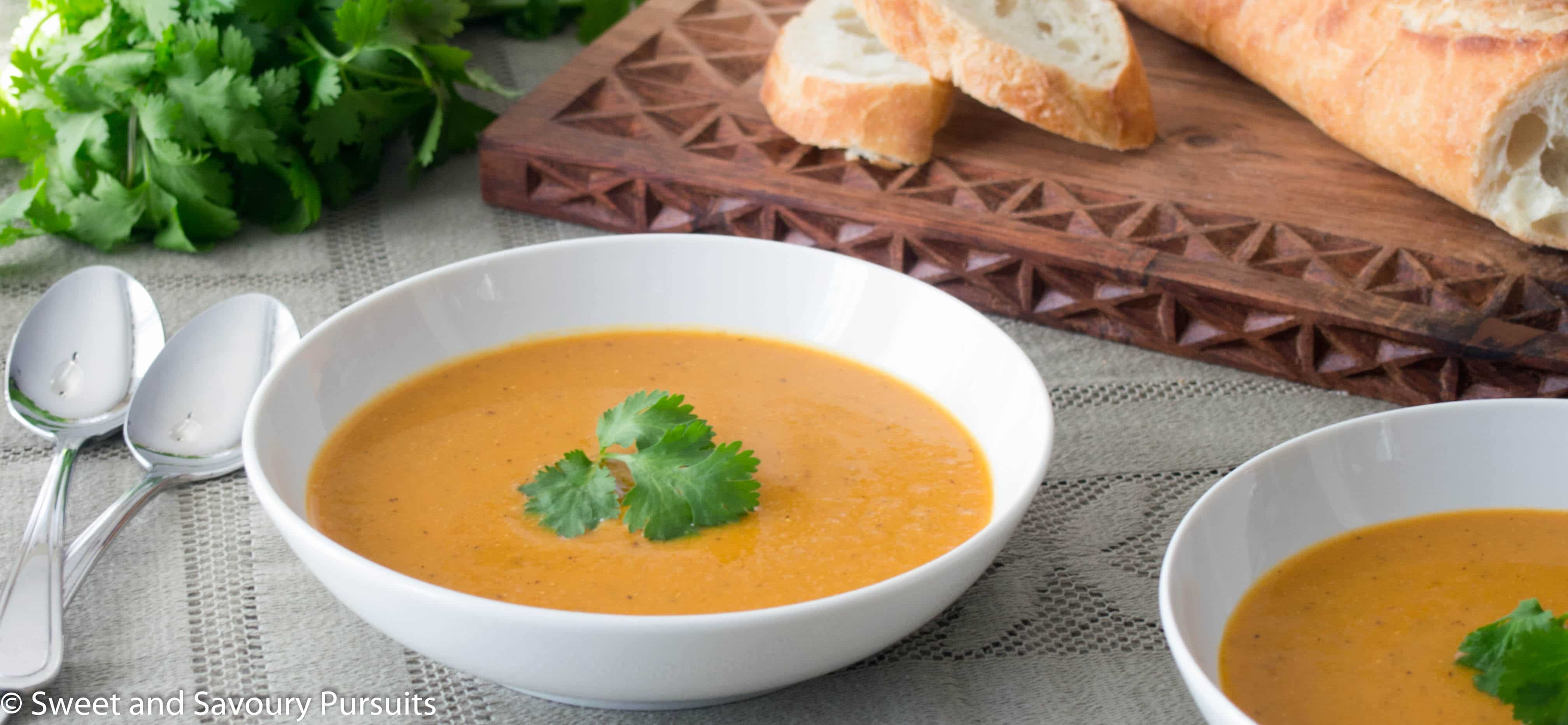 Red Lentil and Cauliflower Soup in white bowls with bread on the side.
