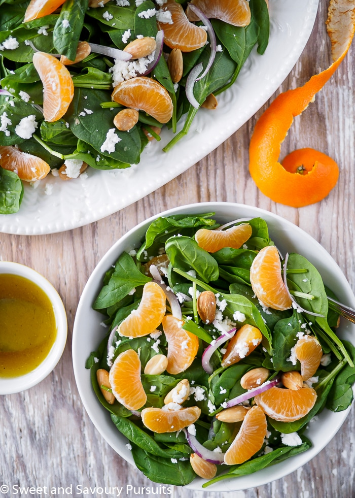 Top view of Spinach Clementine Salad with almonds and goat cheese