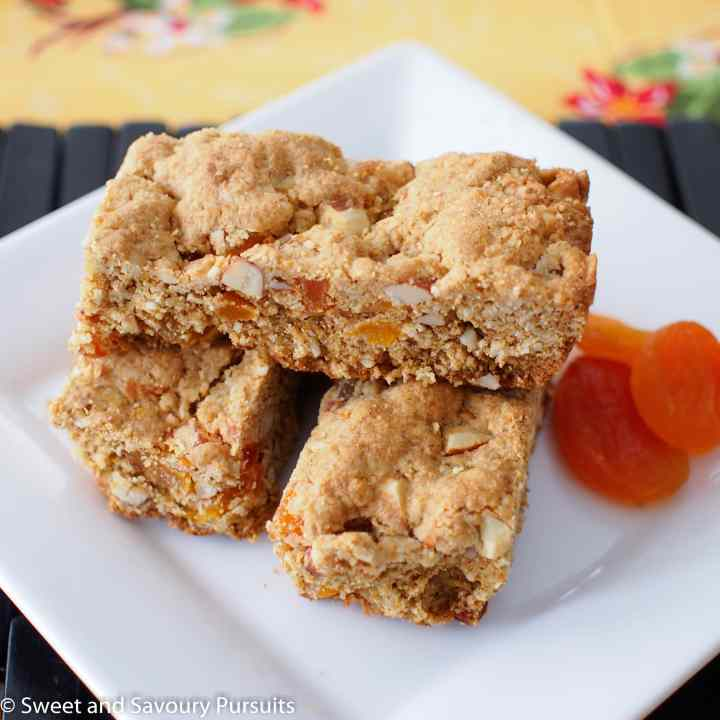 Whole Wheat Apricot and Almond Bars on white dish served with dried apricots on the side.