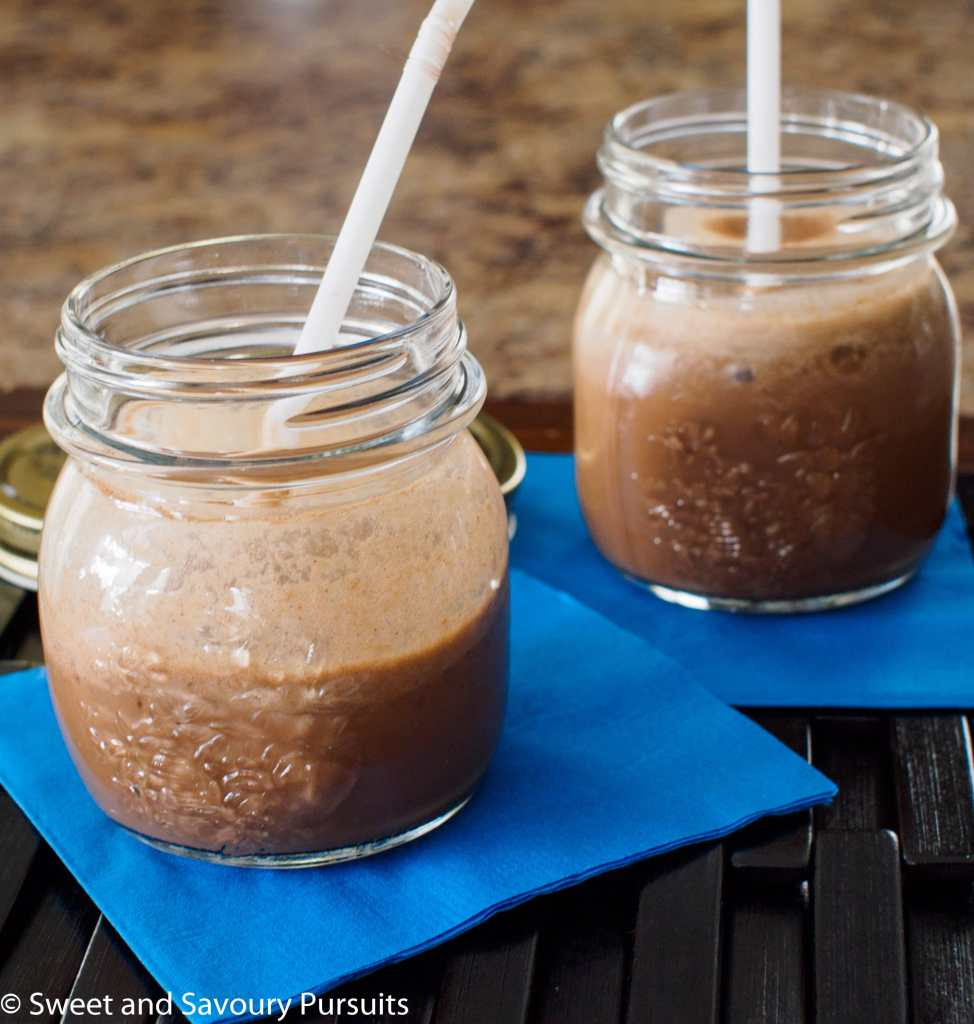 Two servings of a coffee flavored smoothie served in small mason jars.