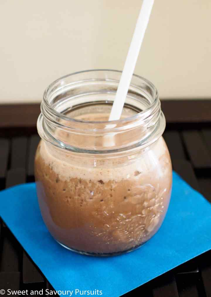An easy and healthy Coffee Smoothie served in small mason jar with straw.