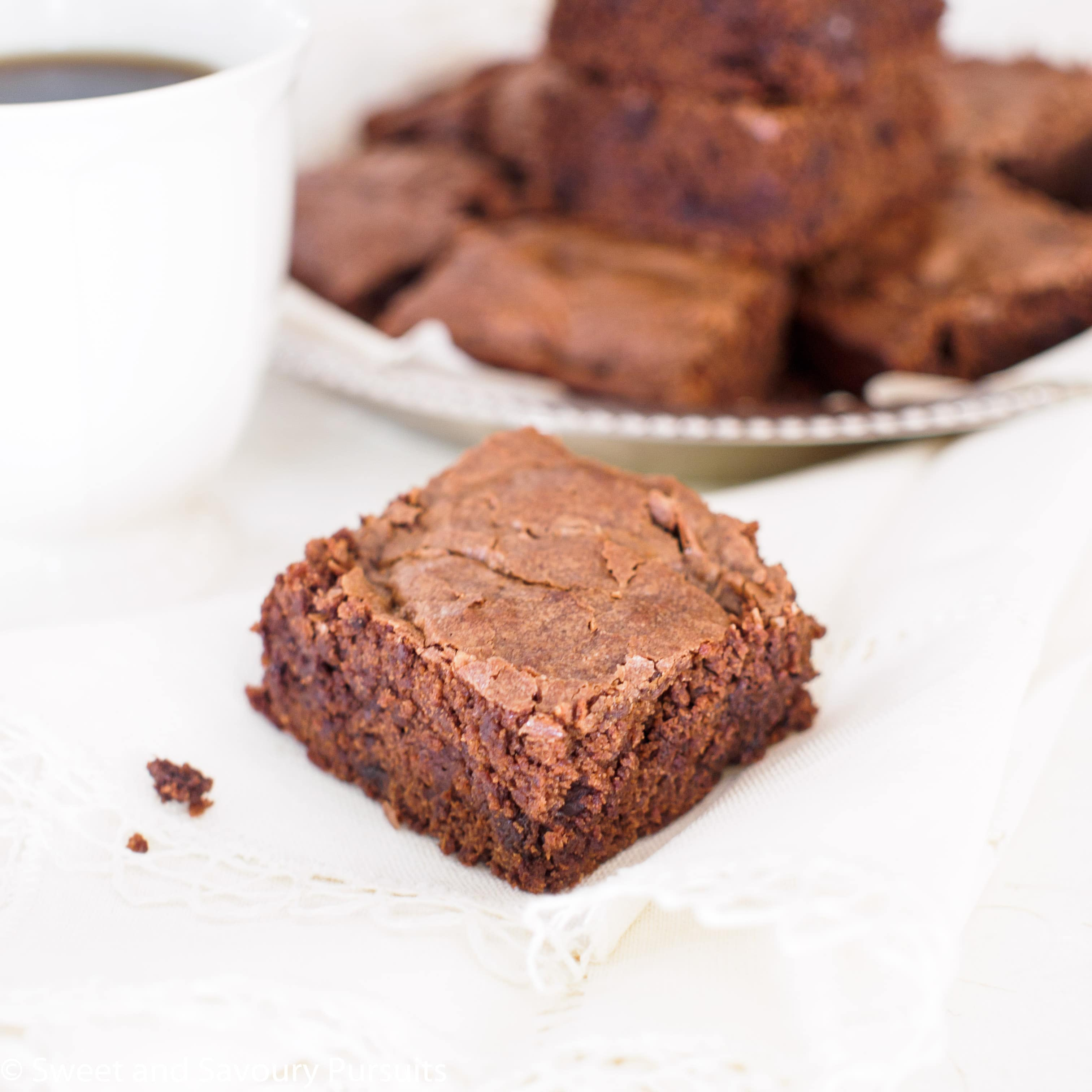 Close up of Triple Chocolate Brownies with cup of coffee and more brownies in background.