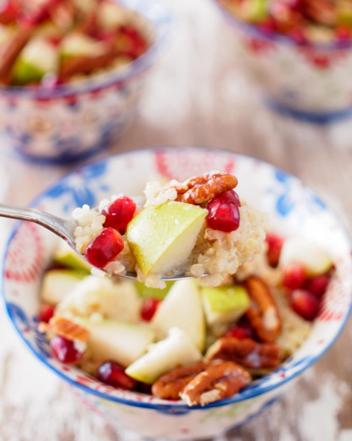 Quinoa Breakfast Bowls topped with pear, pomegranate and pecan pieces.
