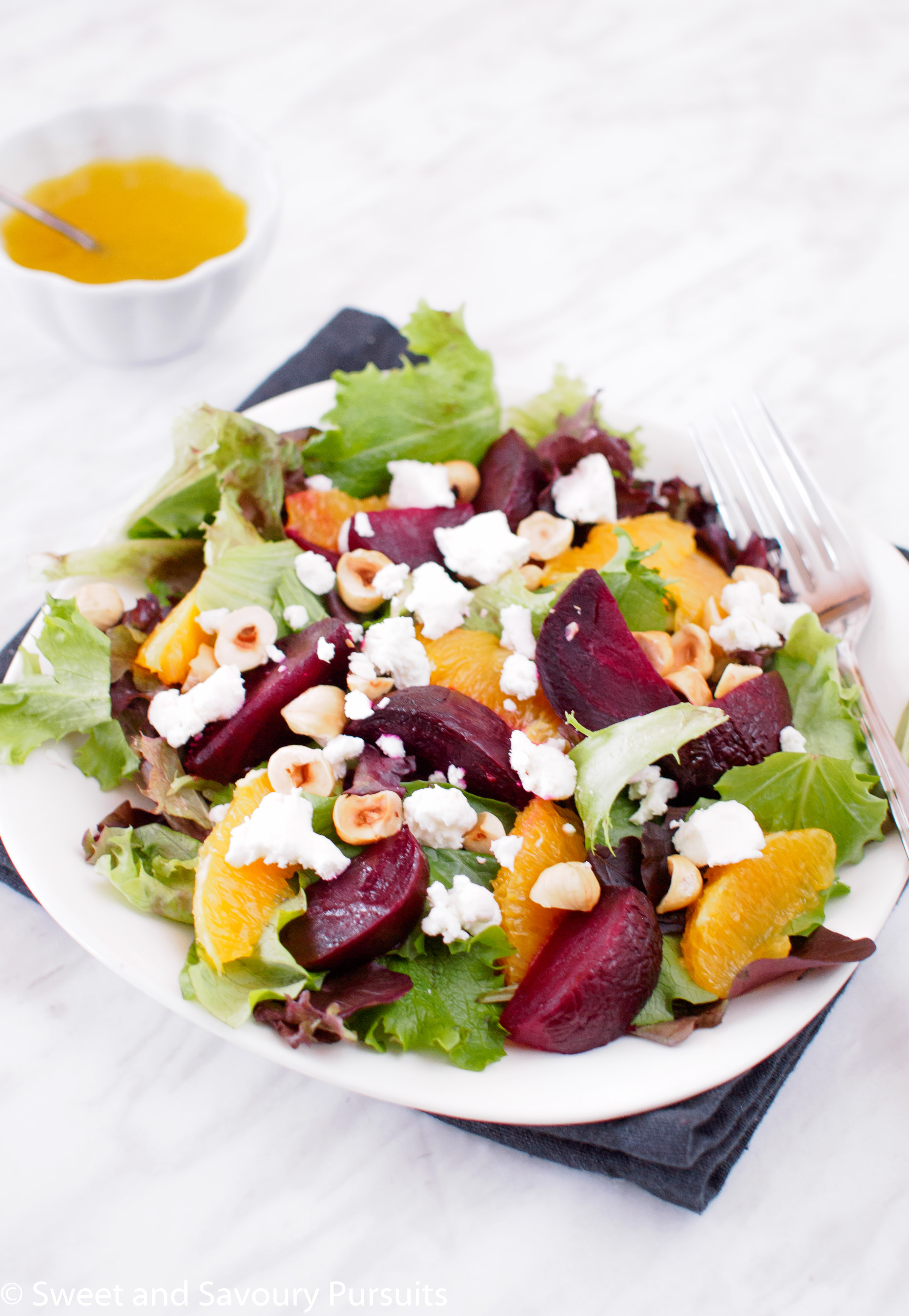 A delicious Roasted Beet and Orange Salad with Citrus Vinaigrette, toasted hazelnuts and creamy goat cheese.