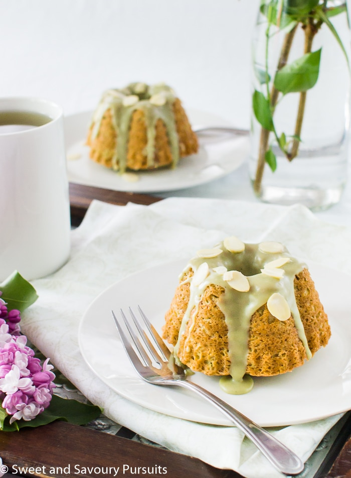 Mini Almond and Matcha Cakes on plates served with a cup of green tea.