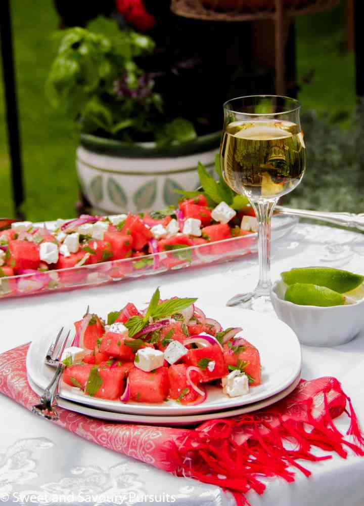 Plate of salad made with watermelon and feta cheese served outdoors.