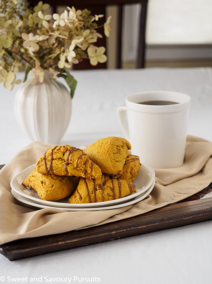 Plate of pumpkin scones served with a cup of coffee.