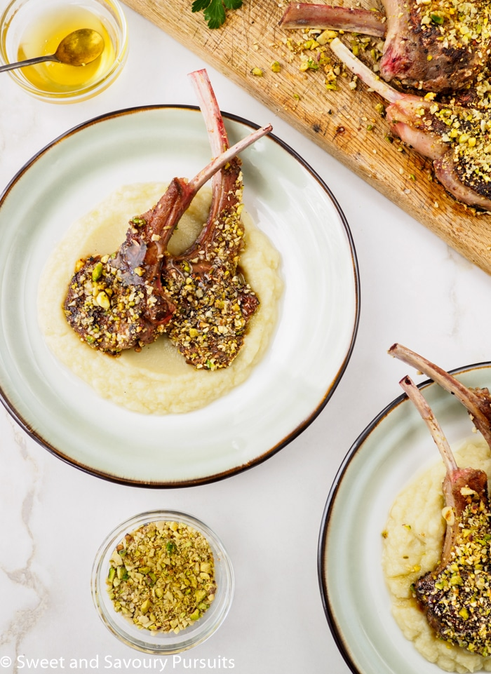 Dish of lamb chops crusted with Dukkah spice mixture served on top of a cauliflower and potato purée.