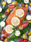 Unbaked rainbow trout fillet on baking sheet with asparagus, cherry tomatoes and zucchini with fresh herbs.