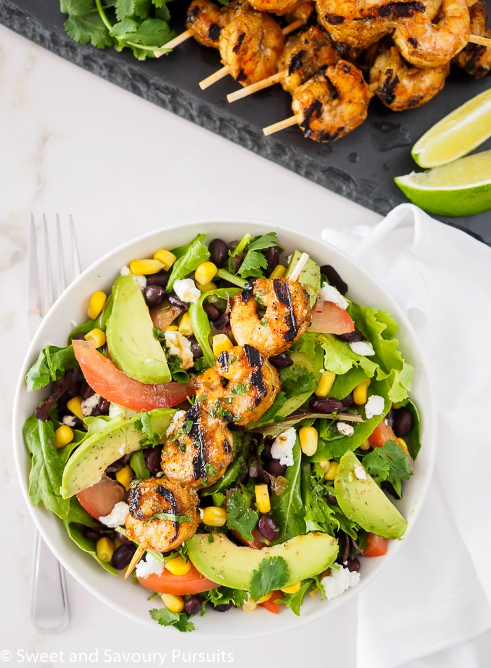 Southwestern Grilled Shrimp Salad served in bowl with extra shrimp and lime on the side.
