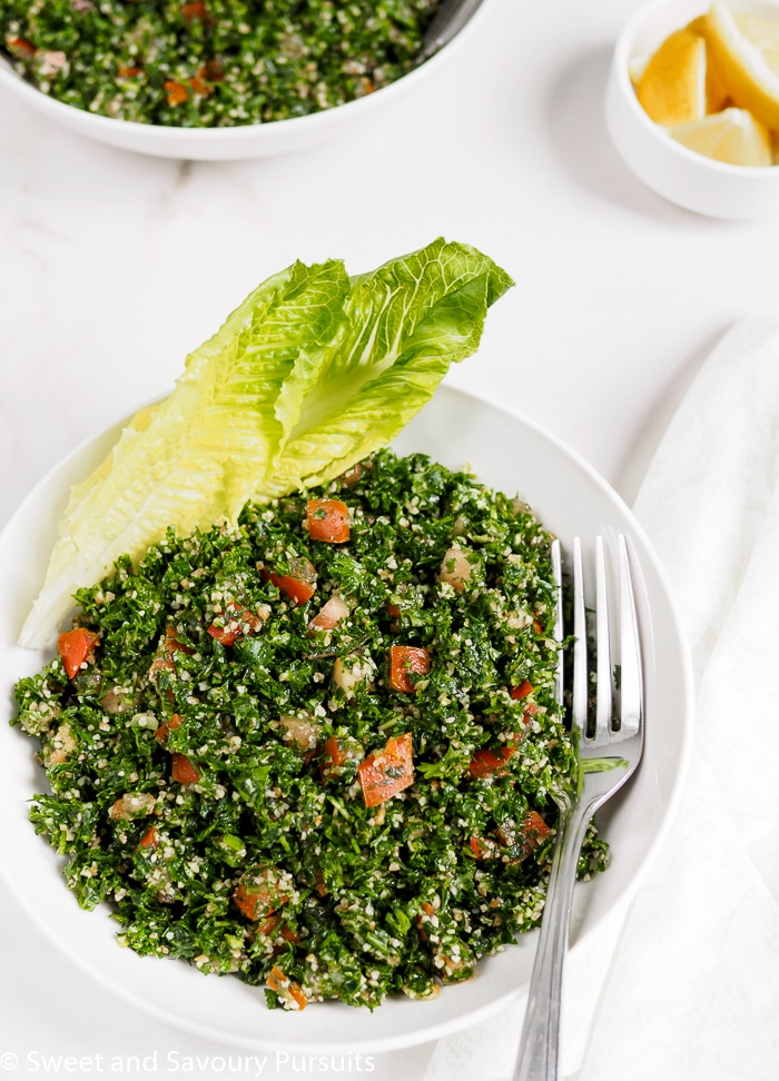 Lebanese Tabbouleh Salad served in white bowl with romaine lettuce leaves to the side.