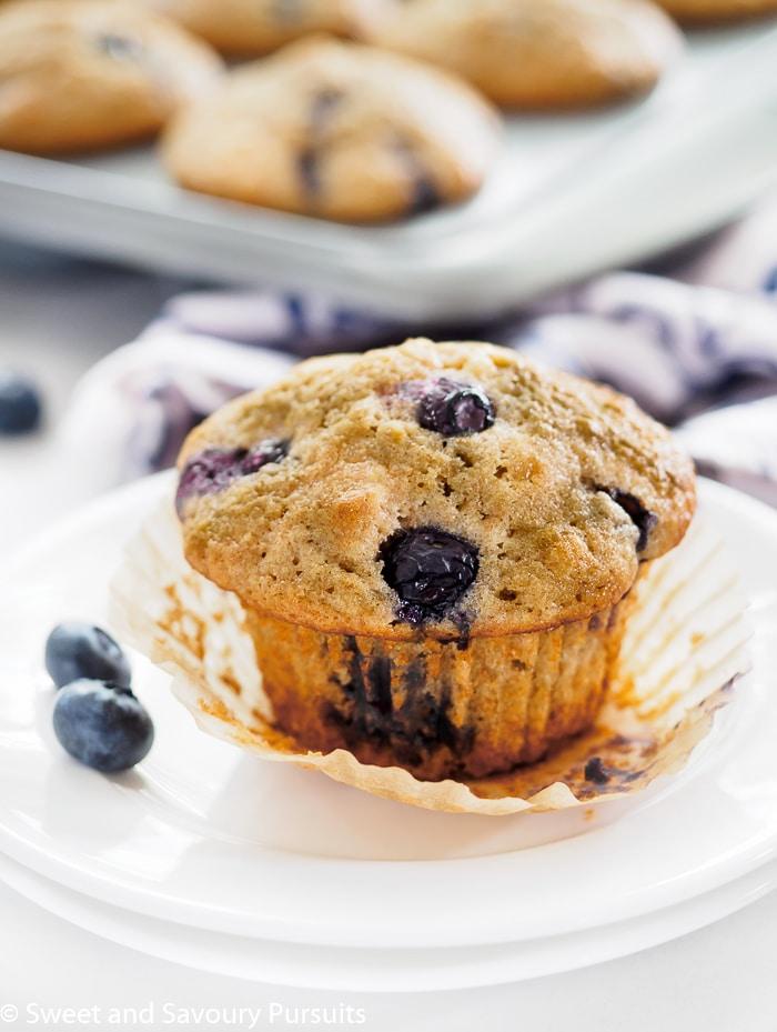 Close-up a Whole Wheat Blueberry Lemon Muffin on a small white dish.
