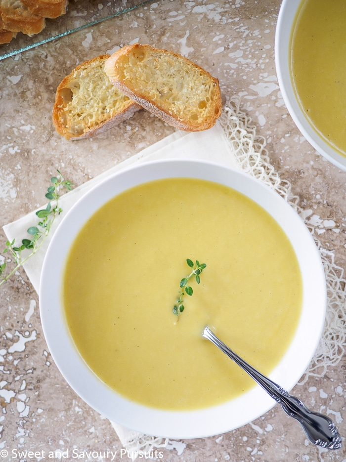 Top view of a bowl of Creamy Leek and Potato Soup served with Garlic Parmesan Crostini