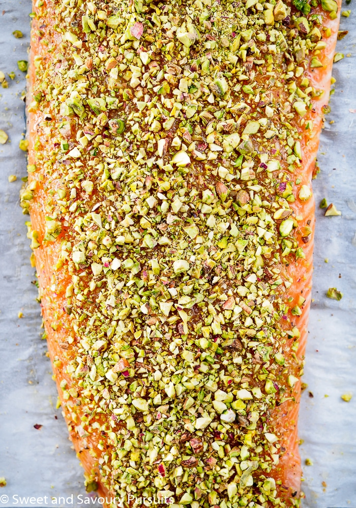 Filet of uncooked salmon with pistachio crust on baking tray.