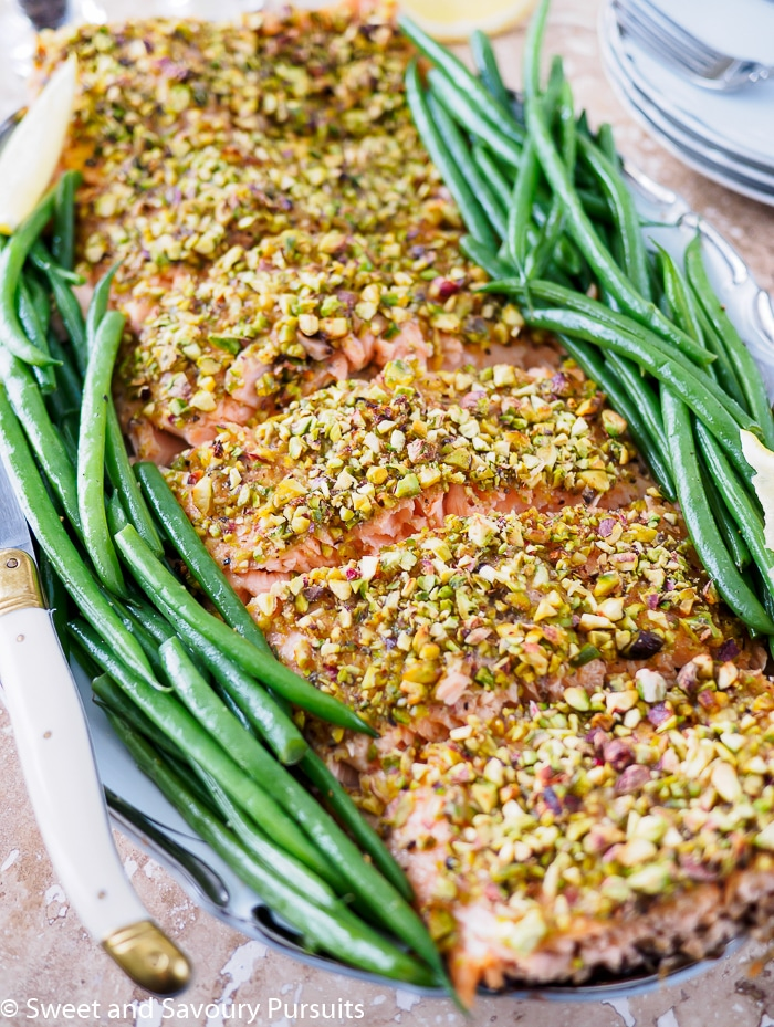 Filet of Pistachio Crusted Salmon and green beans on serving dish.