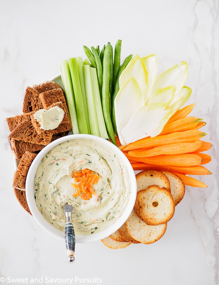 Bowl of Smoked Salmon Cream Cheese Dip served with vegetable pumpernickel bread and crackers.