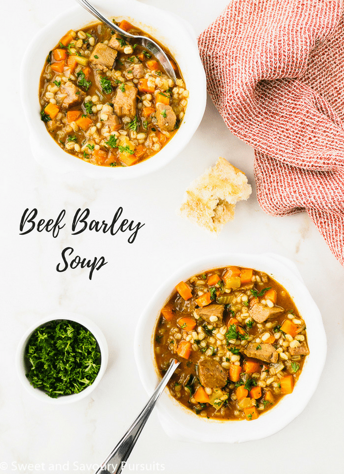 Two bowls of Beef Barley Soup topped with chopped fresh parsley and served with bread.