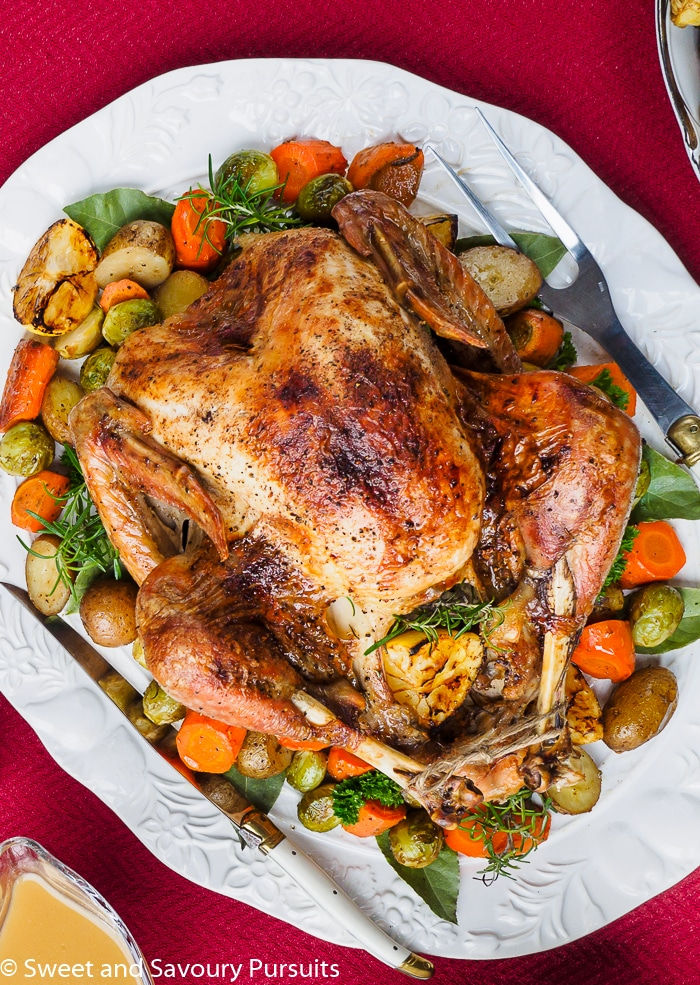 Roast Turkey with vegetables on large white platter with gravy on the side.