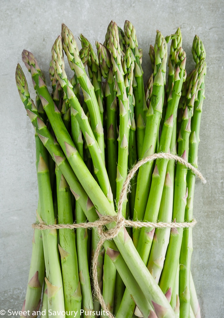 A bunch of asparagus tied with kitchen twine.