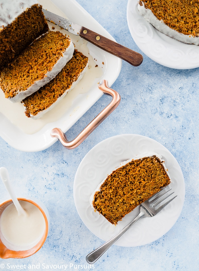 Top view of a Healthy Carrot Bread sliced and served with extra icing on the side.